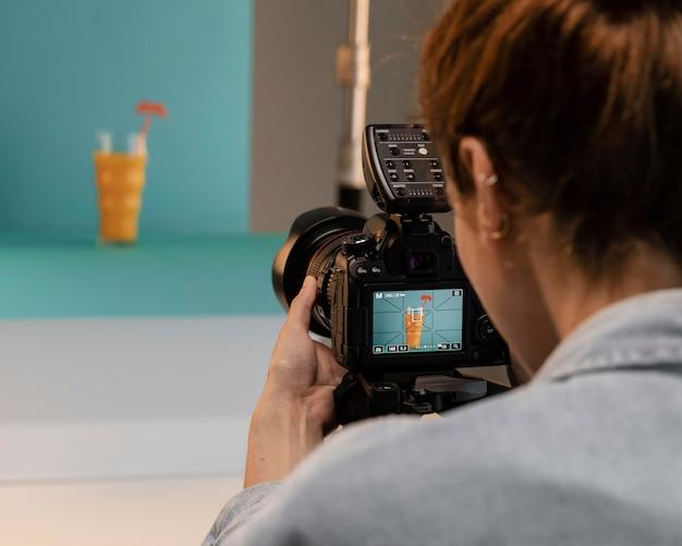 スタジオで若い女性製品写真家