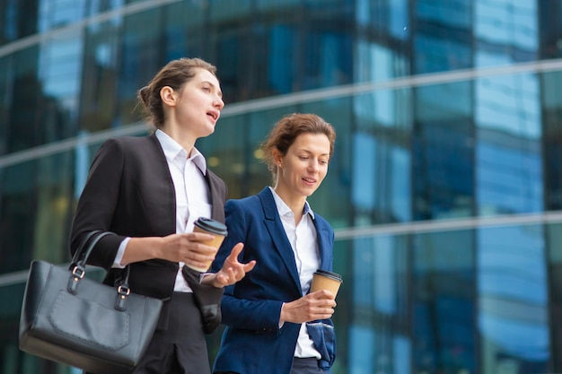 Young female professionals with takeaway coffee mugs wearing office suits, walking together past glass office building, talking, discussing project. medium shot. work break or friendship concept
