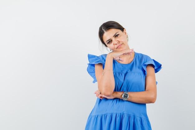 青いドレスを着て手に顎を支え、物思いにふける若い女性