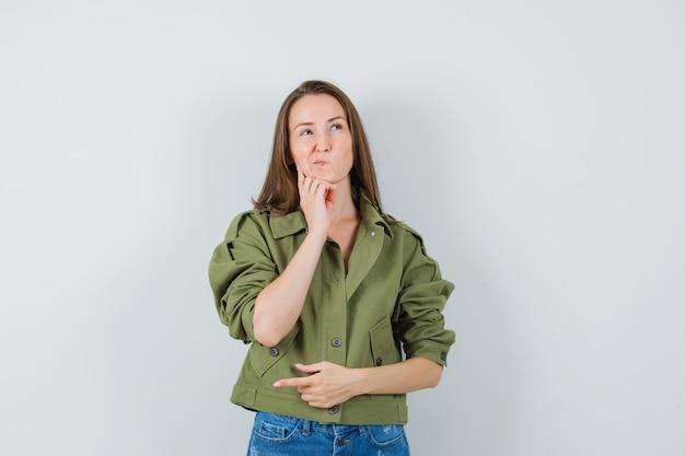 젊은 여성 재킷, 반바지에 손에 턱을지지하고 우유부단 한, 전면보기를 찾고 있습니다.