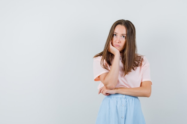 Giovane femmina puntellando il mento sul palmo della mano in t-shirt, gonna e guardando senza speranza, vista frontale.
