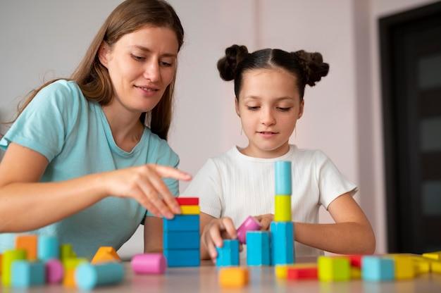 언어 치료에서 소녀를 돕는 젊은 여성 심리학자