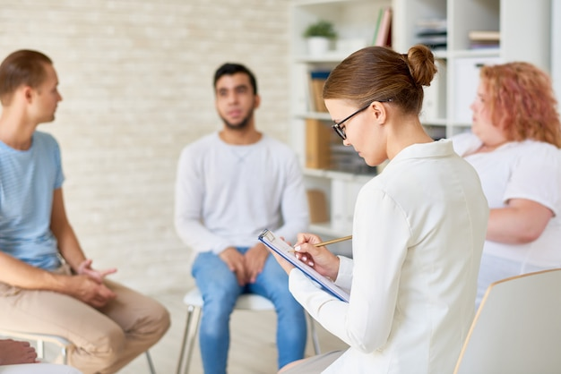 Young female psychologist leading therapy session
