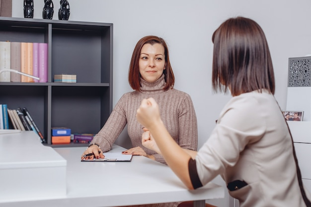 Young female psychologist listens carefully to her client's complaints. client clenched his fists. the help of a psychotherapist.