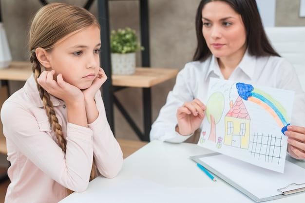 悲しい深刻な少女に描かれた家で紙を描く若い女性心理学者
