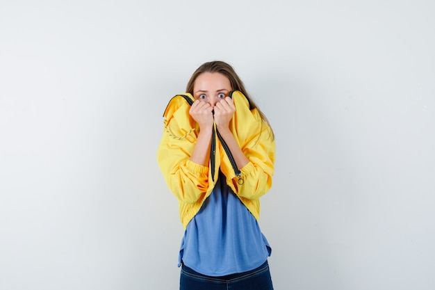 Young female pulling collar on her face in t-shirt, jacket and looking frightened. front view.