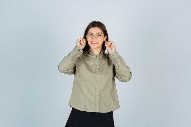 Молодая женщина опускает мочки ушей в рубашке, юбке и выглядит весело