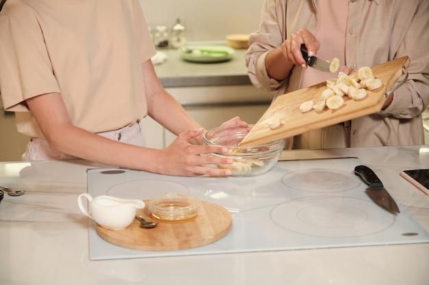 가정 요리 마스터 클래스 동안 다른 아이스크림 재료와 혼합하기 전에 바나나 조각을 유리 그릇에 넣는 젊은 여성