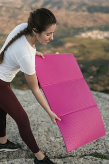 Young female putting yoga mat on mountain