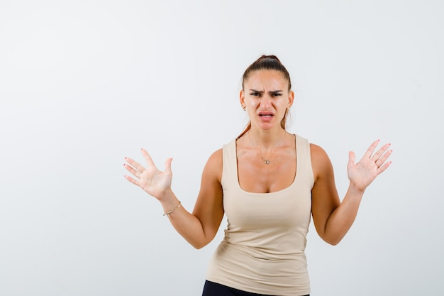 Young female raising hands in aggressive manner in beige tank top and looking angry , front view.