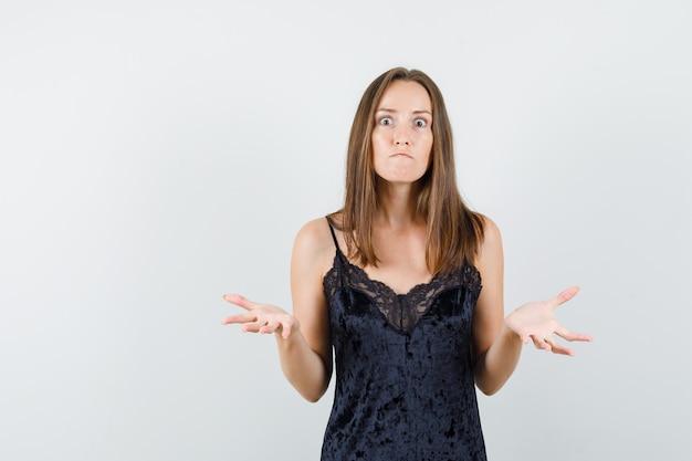 젊은 여성 검은 단일에 적극적인 방식으로 손을 올리고 화가 찾고.