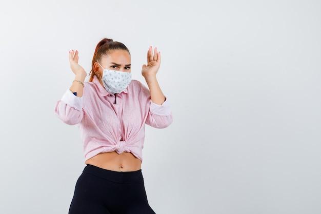 Молодая женщина поднимает руки возле головы в рубашке, штанах, медицинской маске и выглядит подчеркнуто. передний план.