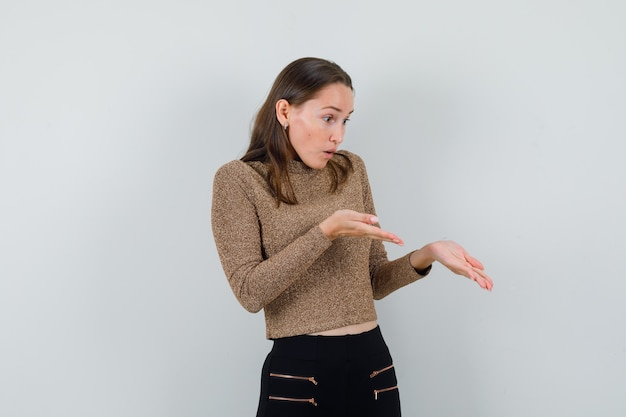 Young female raising hands in questioning manner in golden blouse and looking puzzled. front view.