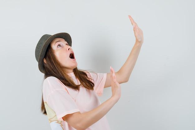 분홍색 티셔츠, 모자에 자신을 방어하기 위해 손을 올리는 젊은 여성은 놀라움을 금치 못합니다. 전면보기.