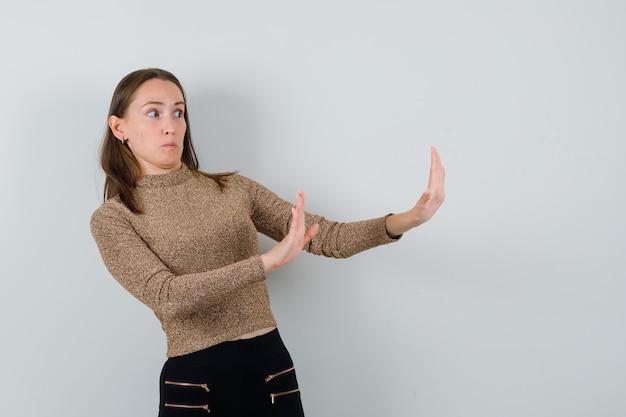 황금 블라우스에 무언가를 거부하고 꺼려하는 동안 손을 올리는 젊은 여성. 전면보기.