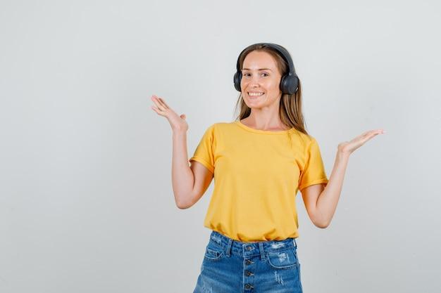 Tシャツ、ショートパンツ、ヘッドフォンで開いた手のひらを上げて幸せそうに見える若い女性。正面図。