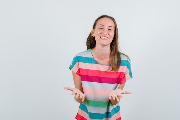 Молодая женщина поднимает ладони в вопросительном жесте в футболке и выглядит позитивно, вид спереди.