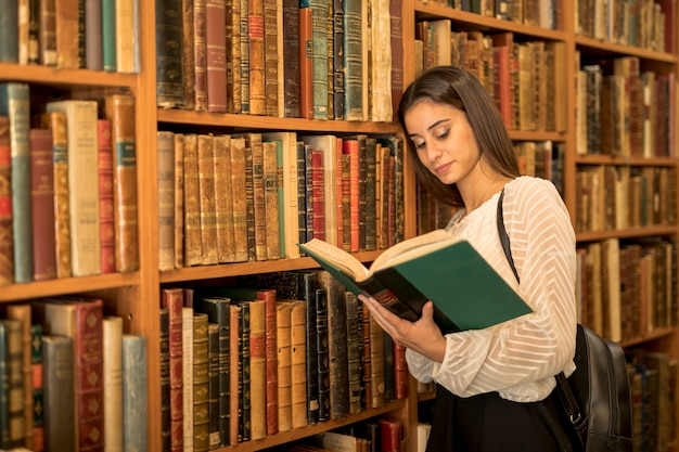 Young female reading book and leaning on shelf
