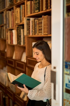 Young female reading book near bookshelf in library