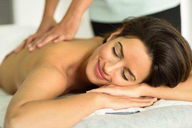 Молодая женщина получает расслабляющий массаж спины в спа-центре.