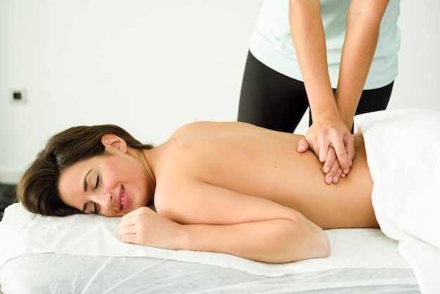 Young female receiving a relaxing back massage in a spa center.
