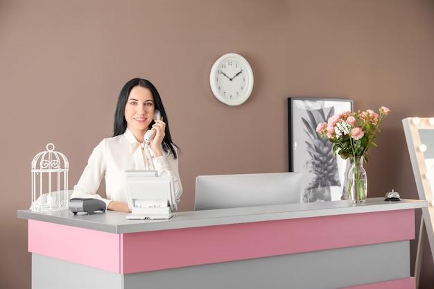 호텔 책상에서 전화로 말하는 젊은 여성 접수원