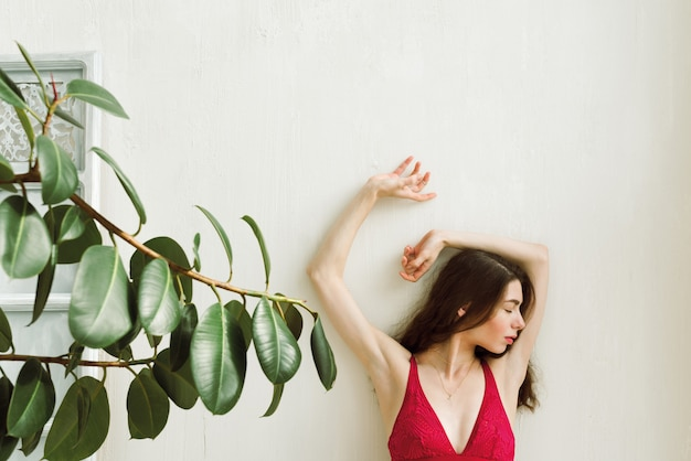 Young female in red bralette with her hands on the white wall