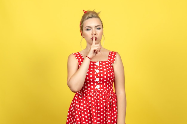 Young female in red polka dot dress asking to be quiet on yellow