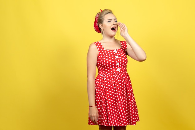 Young female in red polka dot dress calling someone on yellow