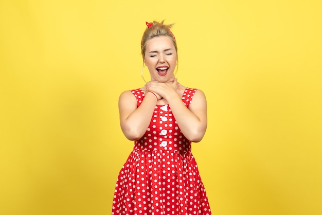 Young female in red polka dot dress chocking herself on yellow