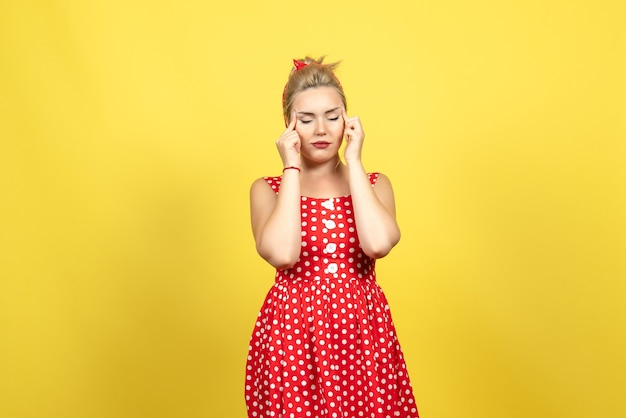 Young female in red polka dot dress closing her eyes on yellow
