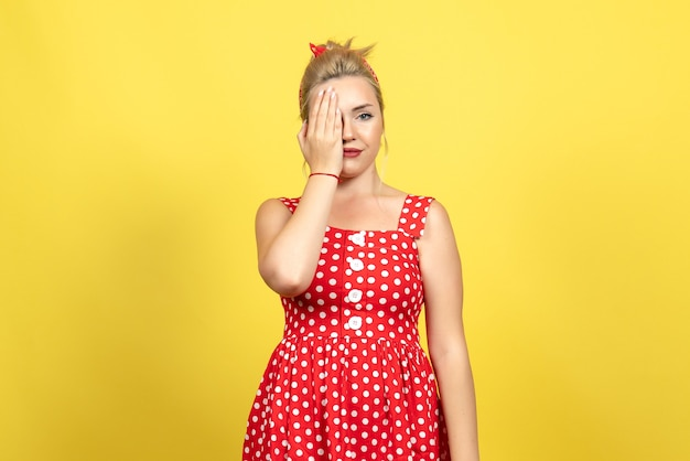 Young female in red polka dot dress covering half of her face on yellow