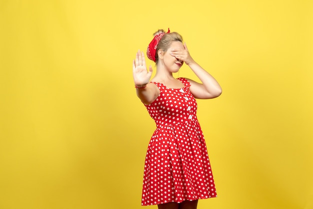 Young female in red polka dot dress covering her face on yellow