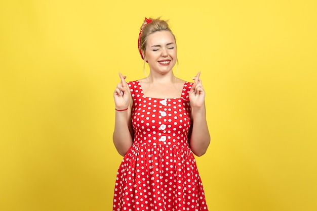 Young female in red polka dot dress crossing her fingers on yellow