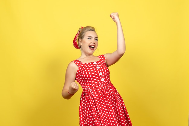 Young female in red polka dot dress emotionally posing on yellow