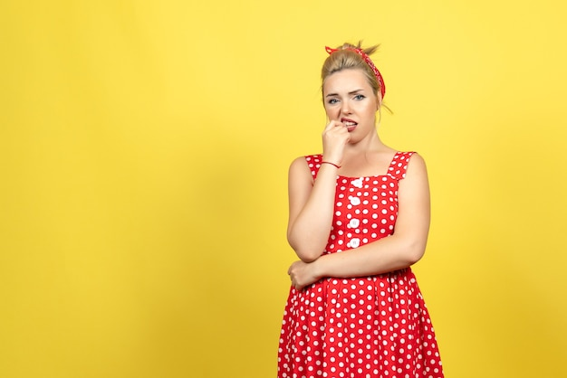 Young female in red polka dot dress feeling nervous on yellow