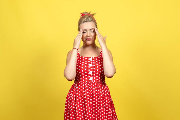Young female in red polka dot dress feeling sad on yellow