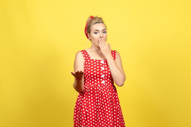 Young female in red polka dot dress feeling surprised on yellow