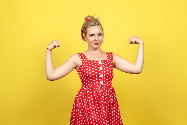 Young female in red polka dot dress flexing on yellow