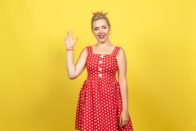 Young female in red polka dot dress greeting someone on yellow