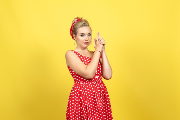 Young female in red polka dot dress and gun holding pose on yellow