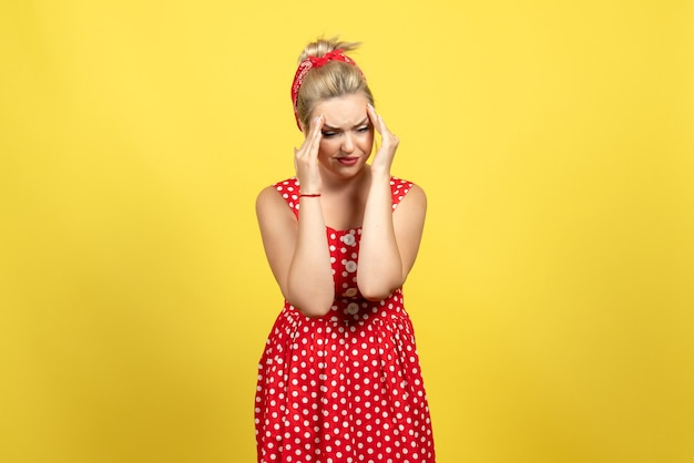 Young female in red polka dot dress having headache on yellow