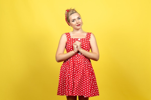 Giovane donna in abito rosso a pois solo in piedi sul giallo