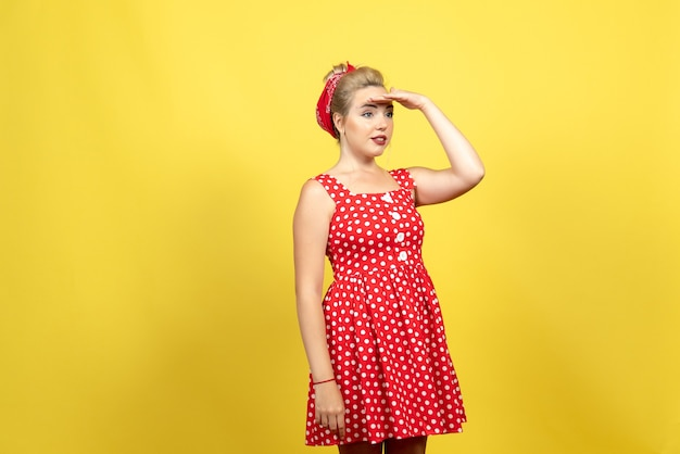 Young female in red polka dot dress looking at distance on yellow