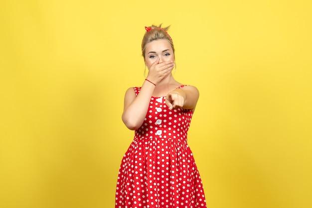 Giovane donna in abito rosso a pois puntando e ridendo sul giallo