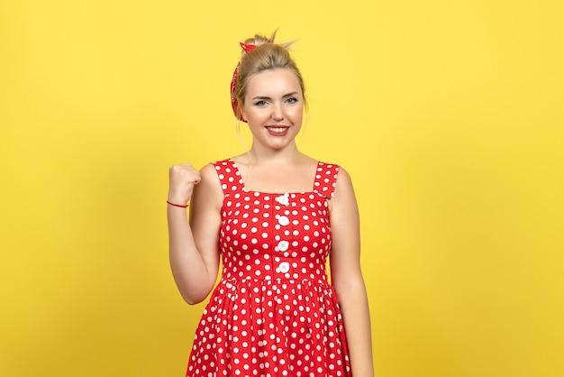 Giovane donna in abito rosso a pois in posa su giallo