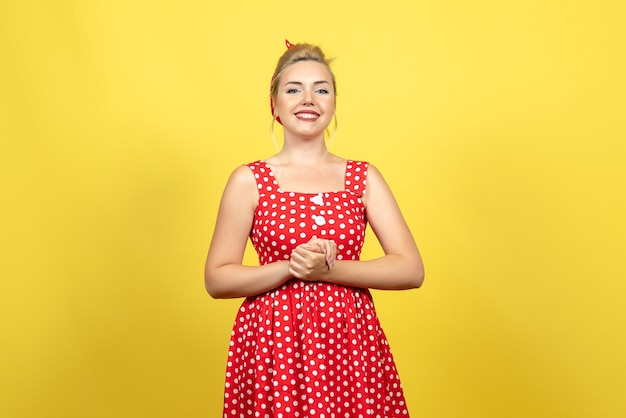 Young female in red polka dot dress posing on yellow