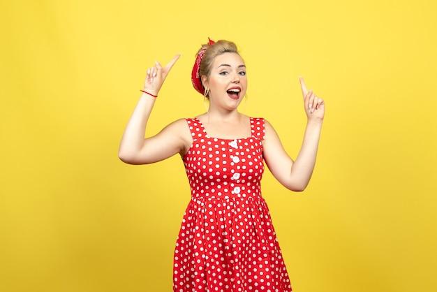 Giovane donna in abito rosso a pois alzando le dita sul giallo