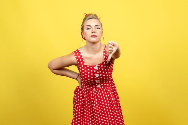 Giovane donna in abito rosso a pois mostrando segno diverso sul giallo
