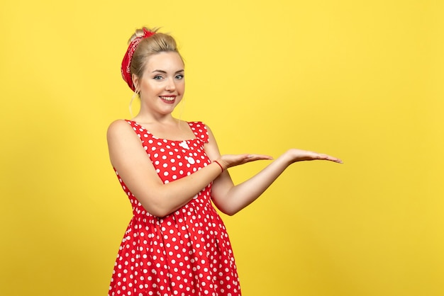 Young female in red polka dot dress smiling on yellow